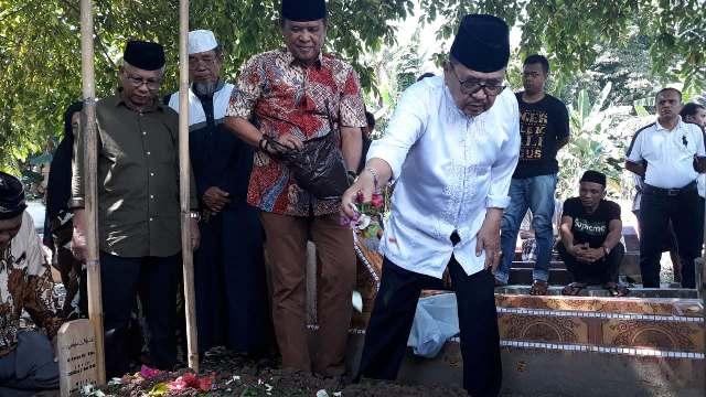 HM Judas Amir didampingi Basmin Mattayang menaburi bunga di atas makam kakaknya usai pemakaman.