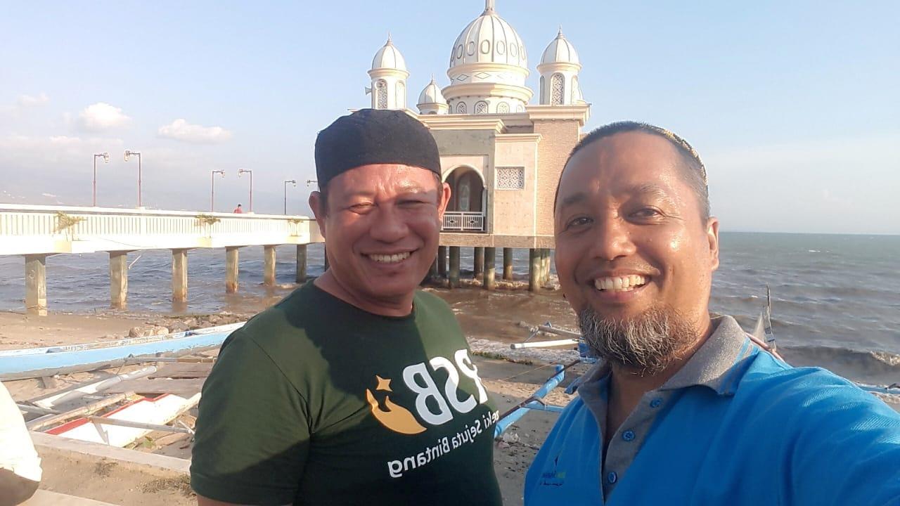 Muhaddar bersama rekannya berfoto di Masjid Terapung kota Palu, beberapa saat sebelum gempa dan tsunami.